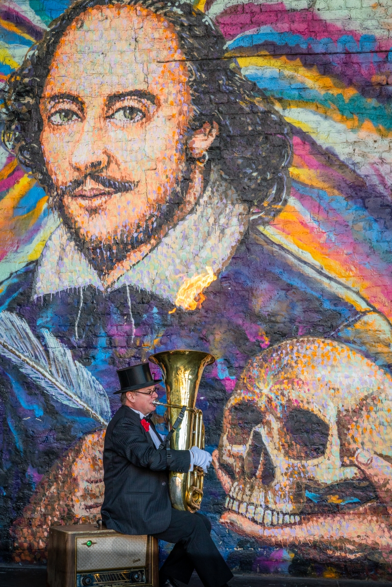 Street performer playing tuba with flames bellowing from top and Shakespeare mural behind