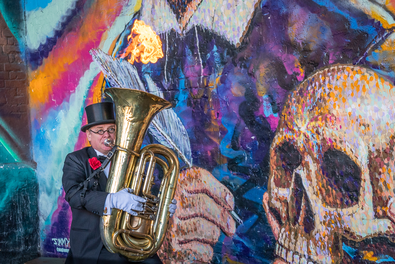 Street performer playing tuba with flames bellowing from top