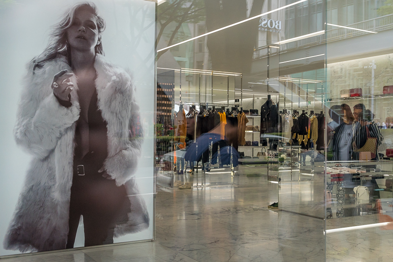 Reflections in YSL shop window with large Kate Moss image inside