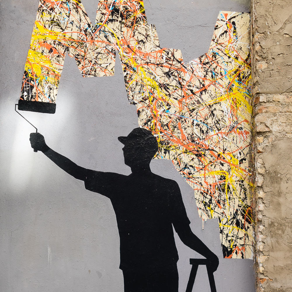 Street art of a man painting the wall