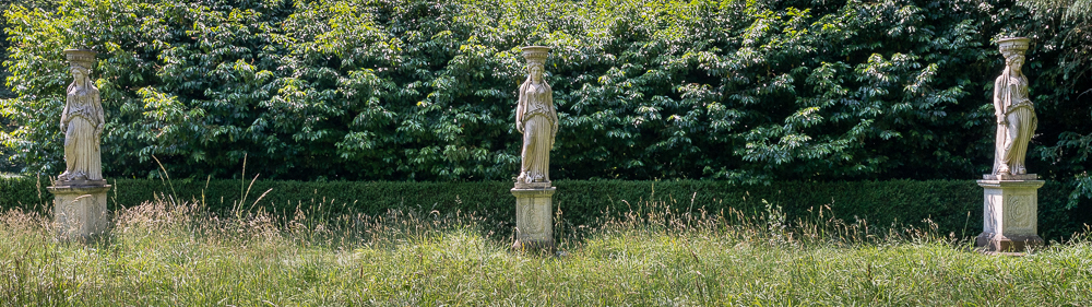 Row of three caryatids in front off a hedge