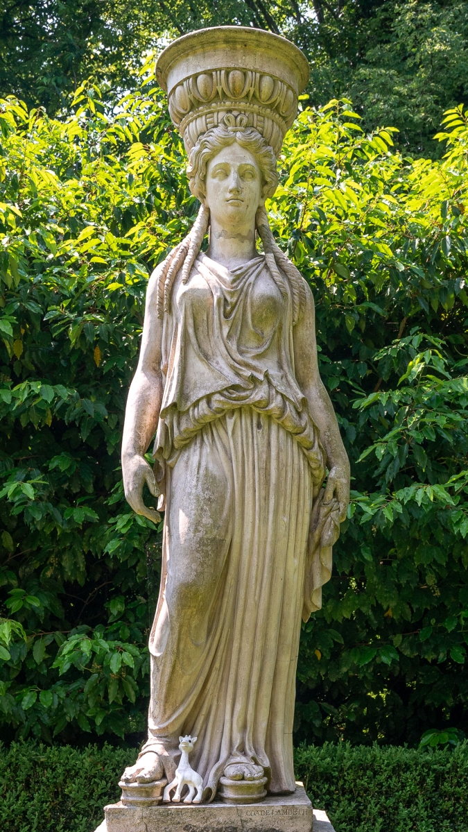 Classic caryatid with small toy giraffe at her feet