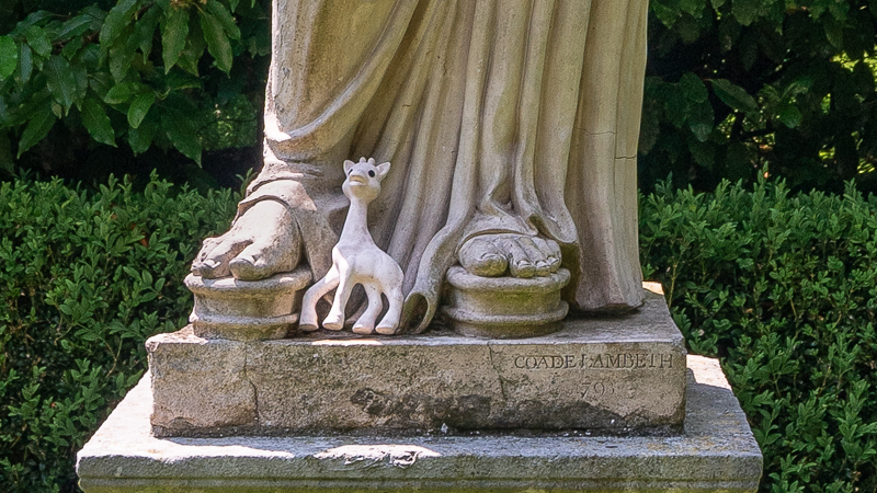 Small toy giraffe at feet of a caryatid