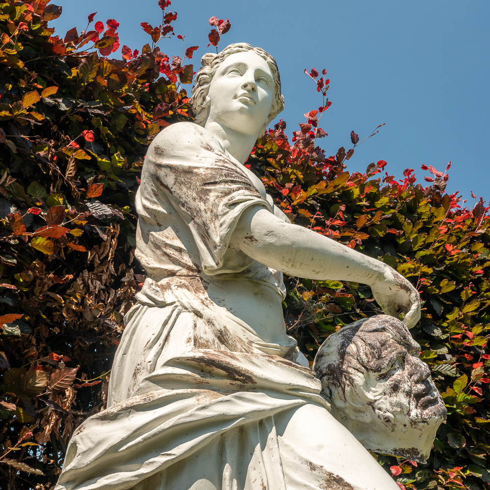 looking up from a low point of view of a woman statue holding a severed head