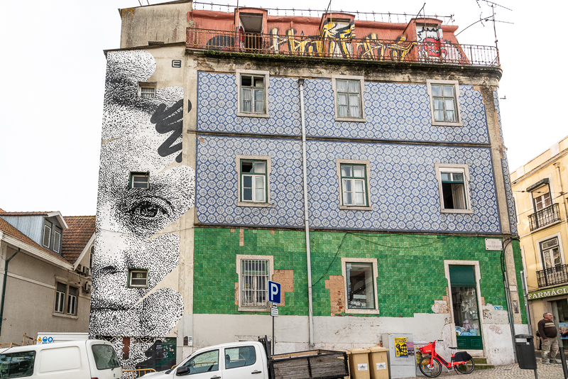 Stencilled black and white mural of the face of Sophia at the end of a building with ceramic tiles