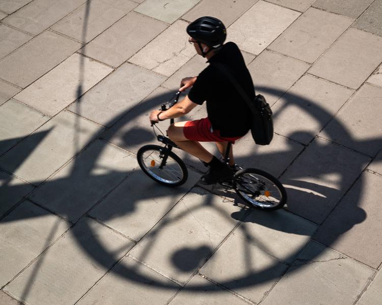 Man cycling through a circular shadow