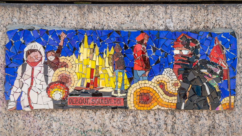 "Mosaic of uprising, people in masks, fire and the words ""Debout! Soulève-toi!"
