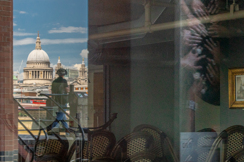 View of St Paul's Cathedral reflected in windows of an empty cafe