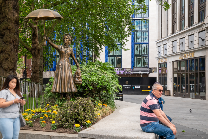 Wider view of statue of Mary Poppins flying under her umbrella in Leicester Square
