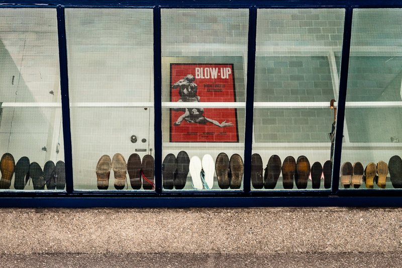 shoes stacked in a window and poster of Blow-up film