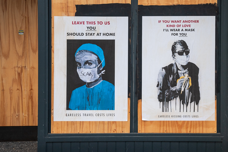 Posters showing protective masks and messages warning that carelessness costs lives