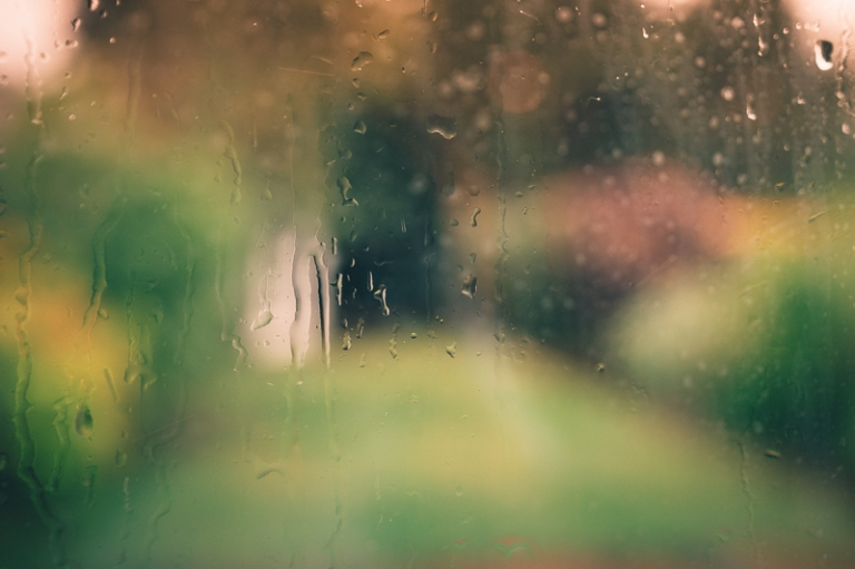 Rain pouring down a window and scene beyond is out of focus with orange glow of sunset
