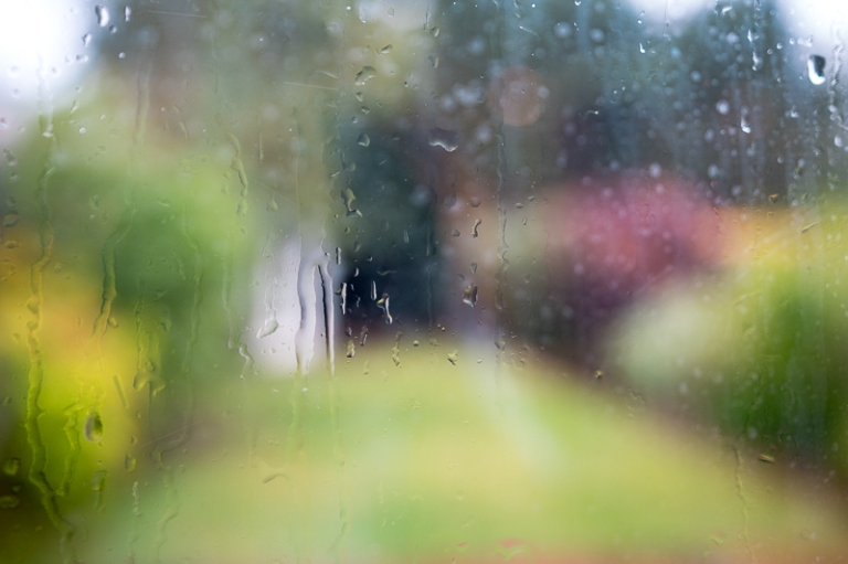 Rain pouring down a window and scene beyond is out of focus