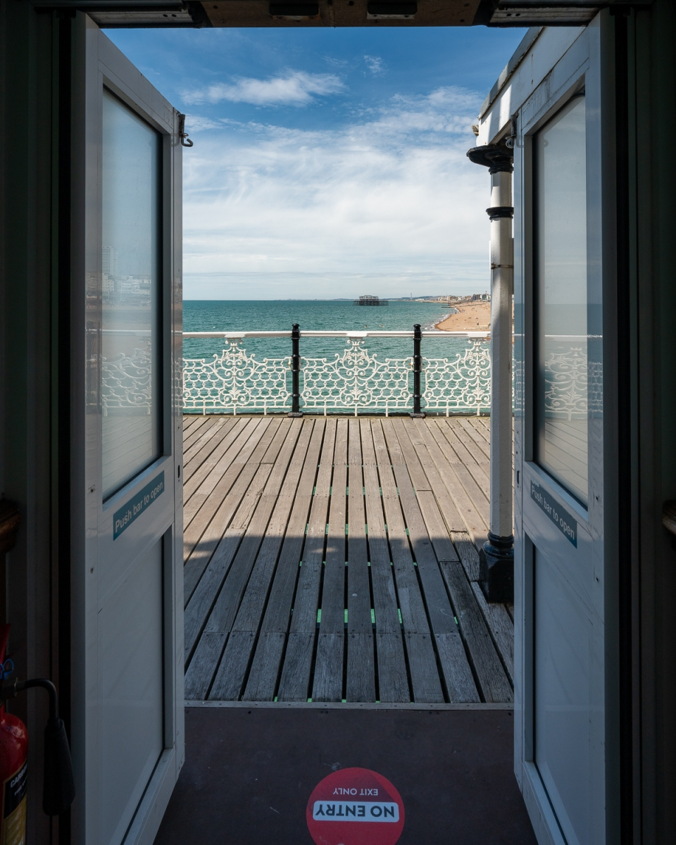 Looking out of arcade on Brighton Palace Pier to West Pier in distance