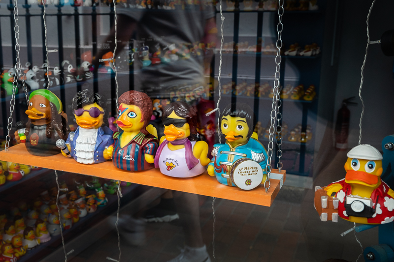 Toy ducks in shop window disguised as famous people and one as a photographer