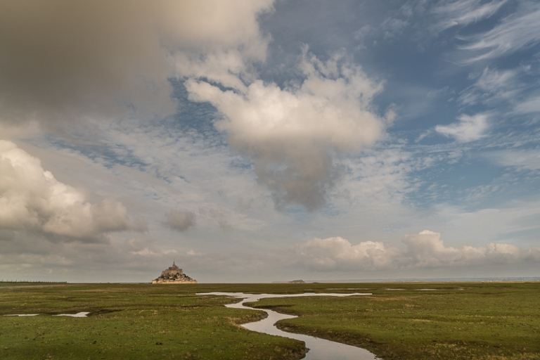 View to Mont St Michel on horizon and cloudy sky above