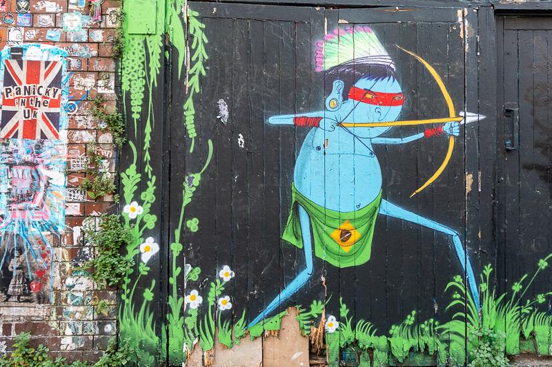 Classic Cranio mural of blue native tribesman shooting an arrow