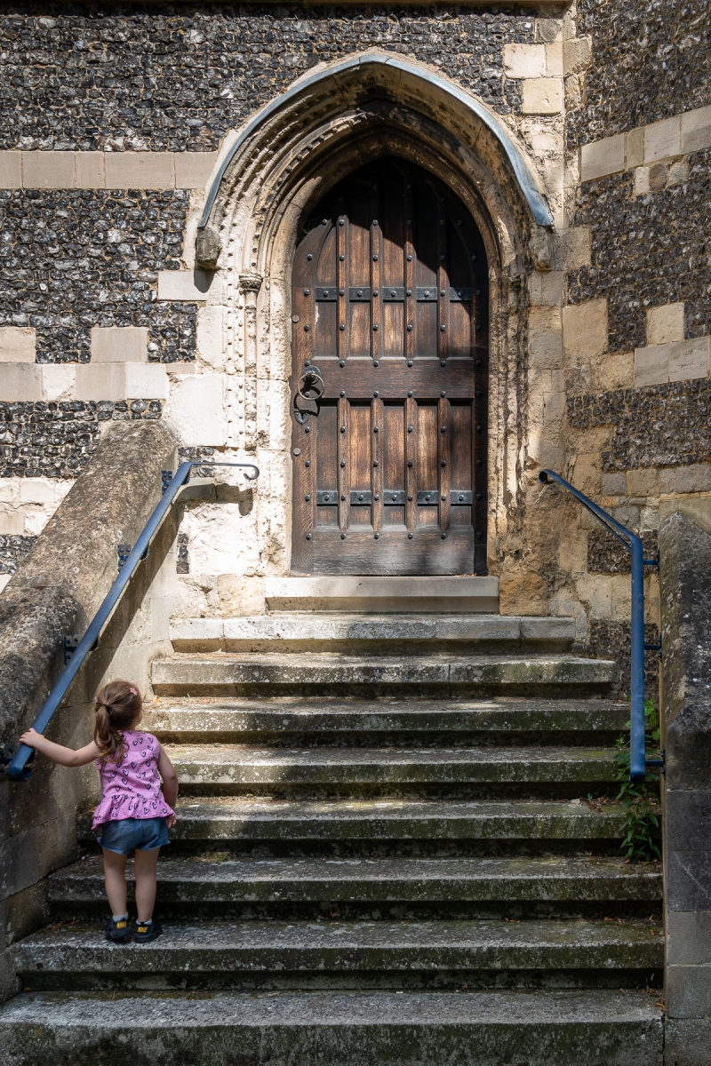 girl climbing steps to an old wooden door