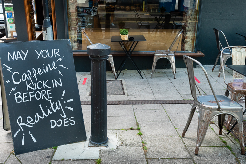"Sign outside a caffeine saying ""May your caffeine kick in before reality does"""