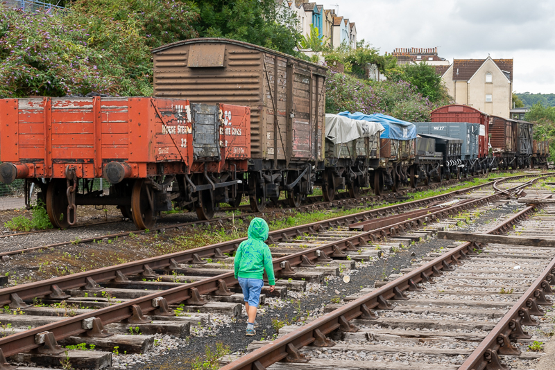 young boy walking along the tracks with old trains beside him