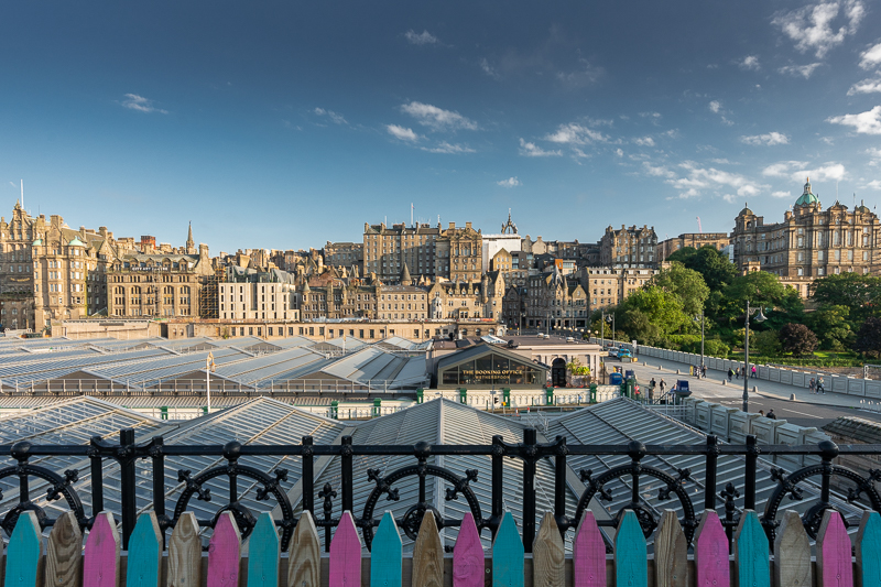 Edinburgh skyline with colourful wooden fence providing a jagged fringe at the bottom