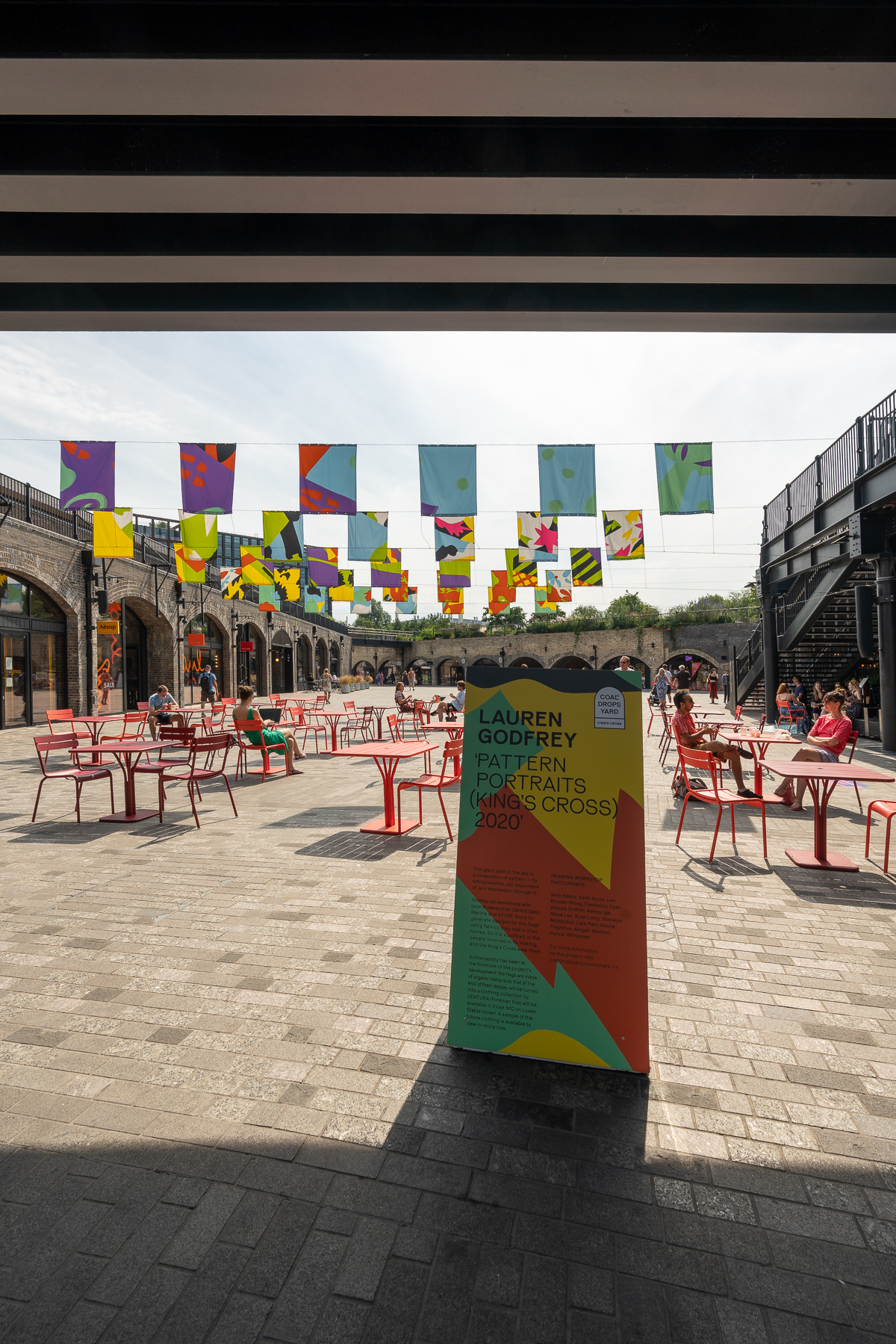 Colourful flags hanging above red tables and chairs at Coal Drops Yard, London
