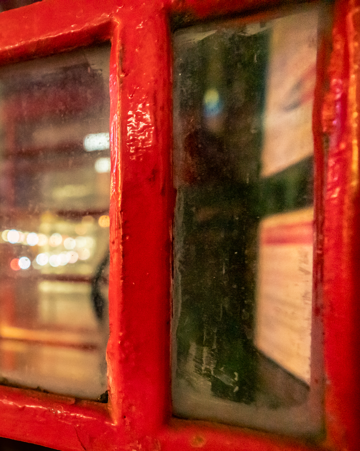 Peeping through the glass of a phone box at night