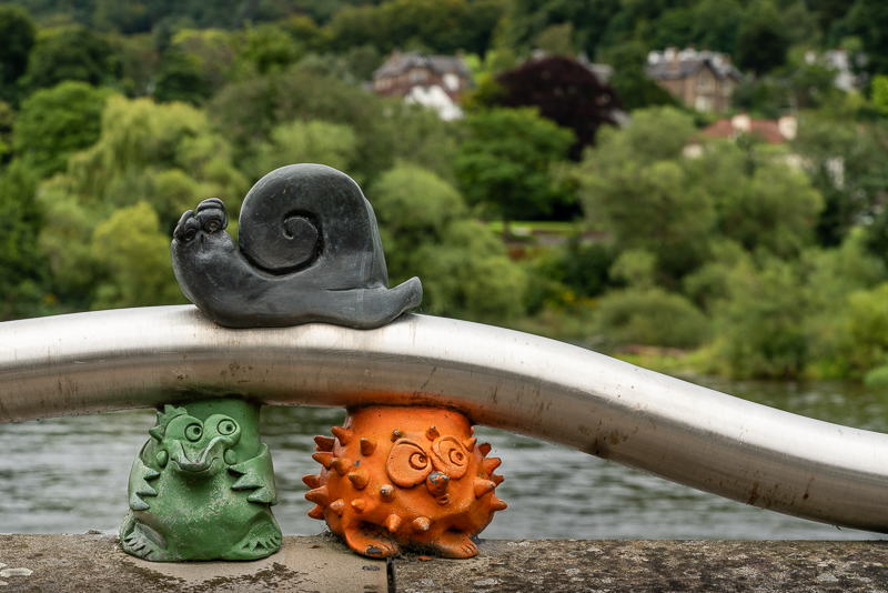 three miniature animal sculptures on edge of river