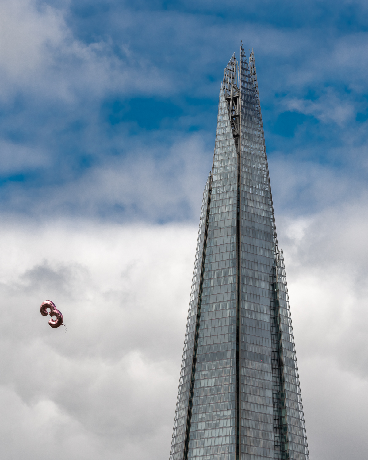 A pink balloon in shape of a 3 flying past The Shard