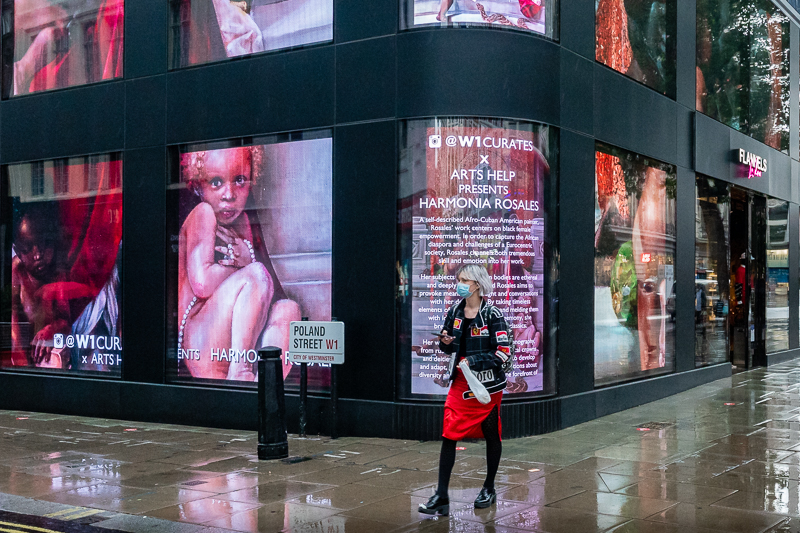 A masked woman standing outside the artistic Flannels store on Oxford street