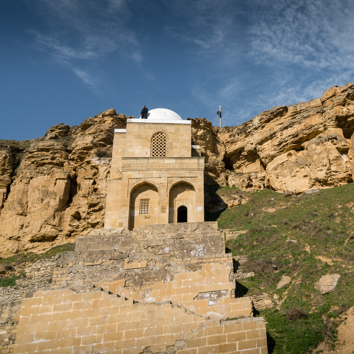 Looking up at a mosque built into a cliff with man on roof