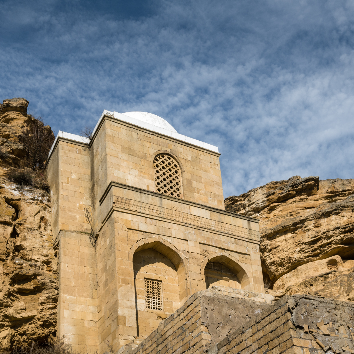 Looking up at a mosque built into a cliff