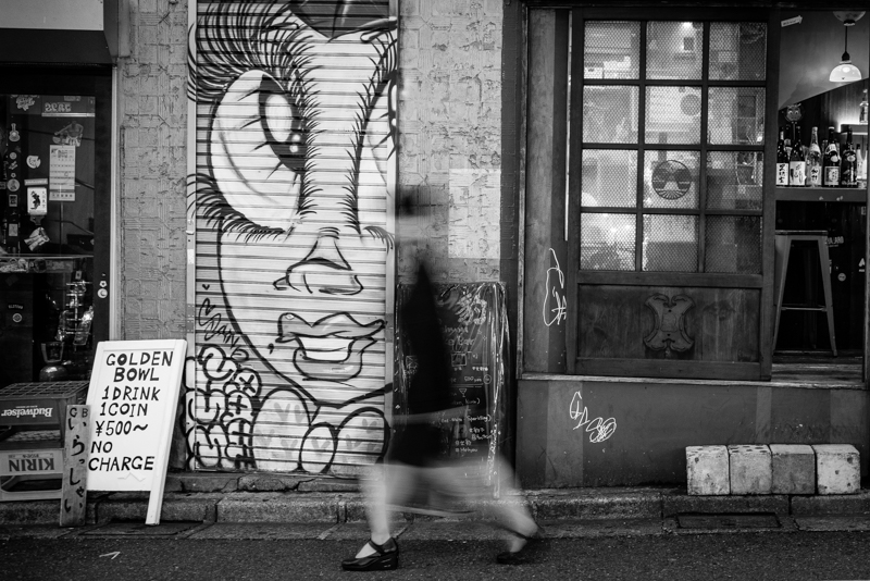 Blurred woman walking past a bar and street art