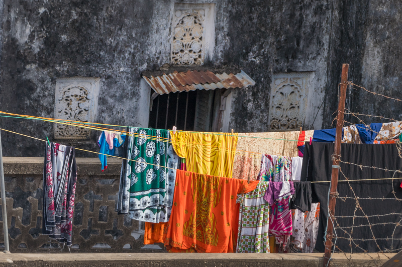 bright clothes on a washing line in front of an old wall in Stone Town