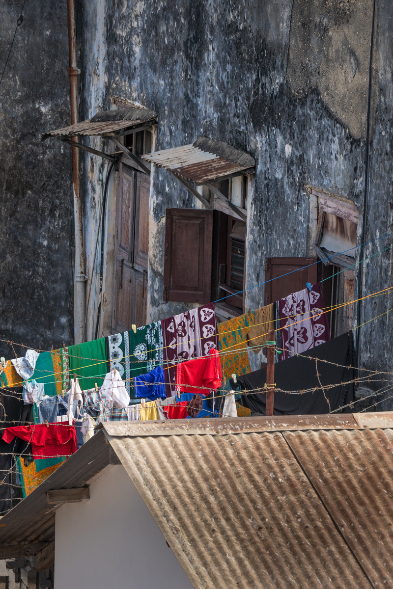 bright clothes on a washing line behind barbed wire in Stone Town