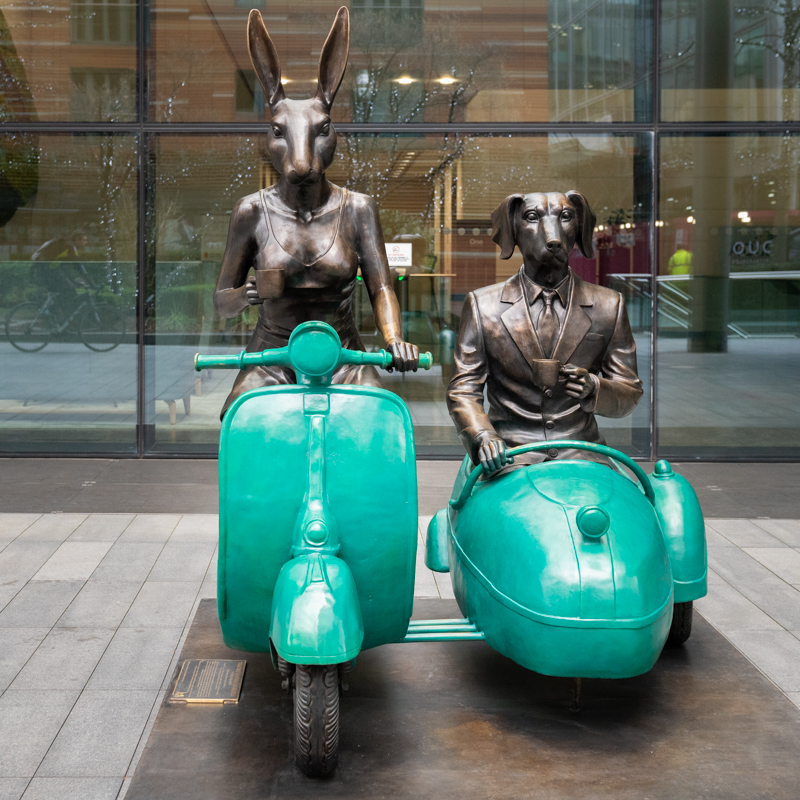 Rabbit and dog statue with cup of coffee on vespa and sidecar