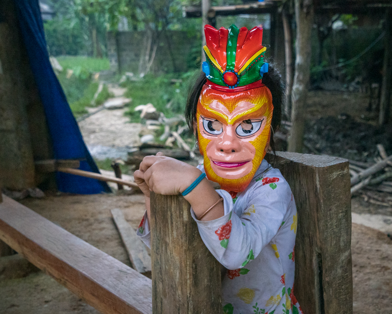 Young child in village wearing a mask
